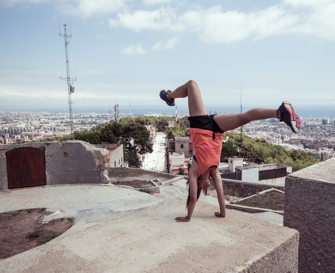 Young woman doing handstand practicing parkour in Barcelona Catalonia Spain